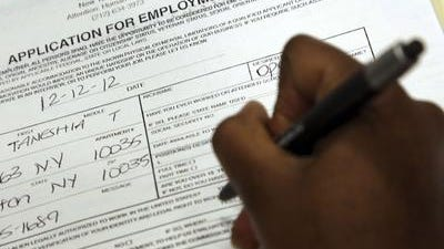 Job seeker fills out a job application during a job fair.