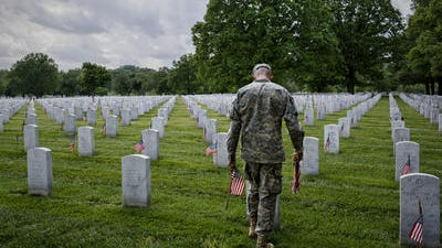 """Spc. Jason McMullen places flags in Section 60 of Arlington National Cemetery during the annual """"flags in"""" ceremony prior to Memorial Day."""
