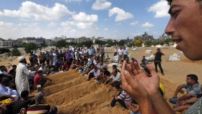 Mourners pray over the graves of members of the Abu Jarad family who were killed in an Israeli strike on their family house, following their funerals in Beit Lahiya, in the northern Gaza Strip, Saturday, July 19, 2014. Eight members of the family were killed.