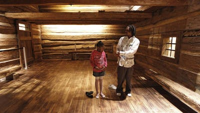 Robert Cooley of College Hill teaches his daughter Cree Rayford, 7, of Avondale the history of the slave house and why chains were used at the National Underground Railroad Freedom Center.