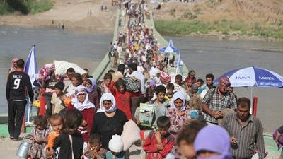 Displaced Iraqis from the Yazidi community cross the Syrian-Iraqi border along the Fishkhabur bridge over the Tigris River at the Fishkhabur crossing, in northern Iraq, on August 13, 2014. At least 20,000 civilians, most of whom are from the Yazidi community, who had been besieged by jihadists on a mountain in northern Iraq have safely escaped to Syria and been escorted by Kurdish forces back into Iraq, officials said. The breakthrough coincided with US air raids on Islamic State fighters in the Sinjar area of northwestern Iraq on August 9, and Kurdish forces from Iraq, Syria and Turkey working together to break the siege of Mount Sinjar and rescue the displaced.