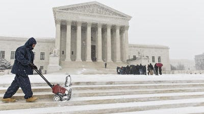 A workman clears snow from the plaza at the U.S. Supreme Court in Washington in Washington, Monday, March 3, 2014, as visitors line up to hear arguments. The Supreme Court has turned away an appeal by the state of Alaska in a long-running fight over the control of rivers and the fishing and hunting rights of Native Alaskans.