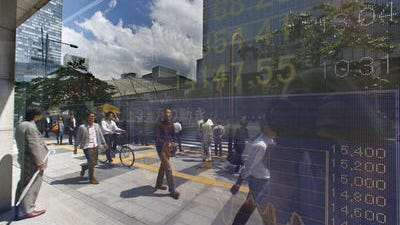 Pedestrians are reflected on the electronic stock indicator of a securities firm in Tokyo Thursday, May 22, 2014. Global stocks mostly rose Wednesday on upbeat data that reinforced confidence in the U.S. economic recovery.