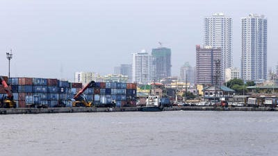 Containers are piled up at the North Harbor on Thursday, May 29, 2014 in Manila, Philippines.World stock markets were mostly weaker Friday after a government report showed the U.S. economy shrank in the first quarter and the U.S. dollar lost value against major Asian currencies.