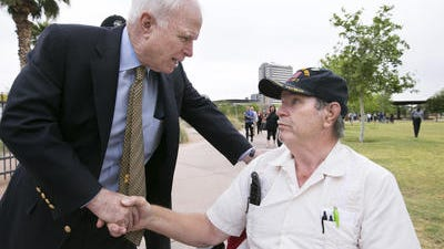 U.S. Sen. John McCain, left, on Friday shakes the hand of Vietnam War veteran Chuck Tharp of Mesa after a news conference at Steele Indian School Park in Phoenix.