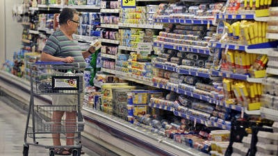 In this June 17, 2014 photo, a shopper looks at an item in the dairy section of a Kroger grocery store in Richardson, Texas. U.S. consumers are more confident about the economy than they have been in more than six years.