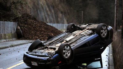 A mudslide caused a rollover crash of a 2006 Kia Optima on River Road S on Tuesday, December 16, 2014, in Salem. The road was closed as the authorities suspected the hillside was still actively moving.