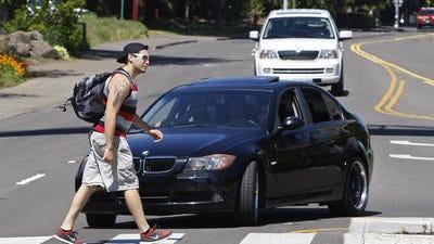 A car making left turn onto the 12th Street NE from Mill Street NE stops to allow a pedestrian to cross using the crosswalk, near Willamette University, on Wednesday, Apr. 30, 2014.