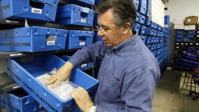 Fotografía de archivo del secretario electoral del condado de Monterey Claudio Valenzuela mientras verifica las boletas que se envían por correo.