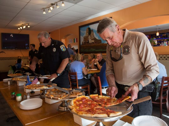 Law enforcement officers grab some slices during the pizza fundraiser at Cosmos Cafe & Pizzeria in Naples on August 3, 2016. The fundraiser benefited the Collier County 100 Club, an organization that provides financial assistance to families of Southwest Florida law enforcement officers and first responders who have died in the line of duty.