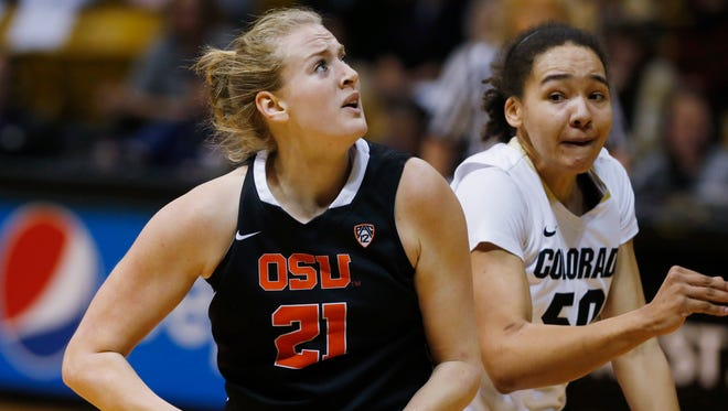 Oregon State center Marie Gulich, left, drives the lane for a shot past Colorado forward Jamee Swan during the first half of an NCAA college basketball game Friday, Feb. 20, 2015, in Boulder, Colo. (AP Photo/David Zalubowski)