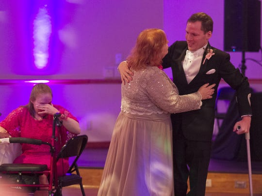 Randy dances with his mom Karen at his wedding reception as his sister Sarah, left, cries. She said she was going to miss her brother being at home with the family.