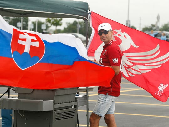 Jozef Kapel of Clark, NJ waits for his grill to heat up standing between the flags of Slovakia and Liverpool FC as fans in the parking lot of MetLife Stadium get ready for the International Champions Cup with Manchester City taking on Liverpool F.C. July 25, 2018. East Rutherford, NJ
