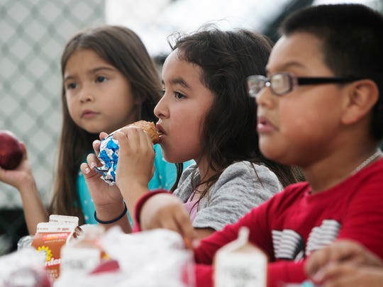 Isabella Cervantes partakes in a meal at the Pine Manor Community Center on Tuesday. Free lunches are given to those in need no questions asked. They are provided by the Lee County School distric in partnership with the USDA.