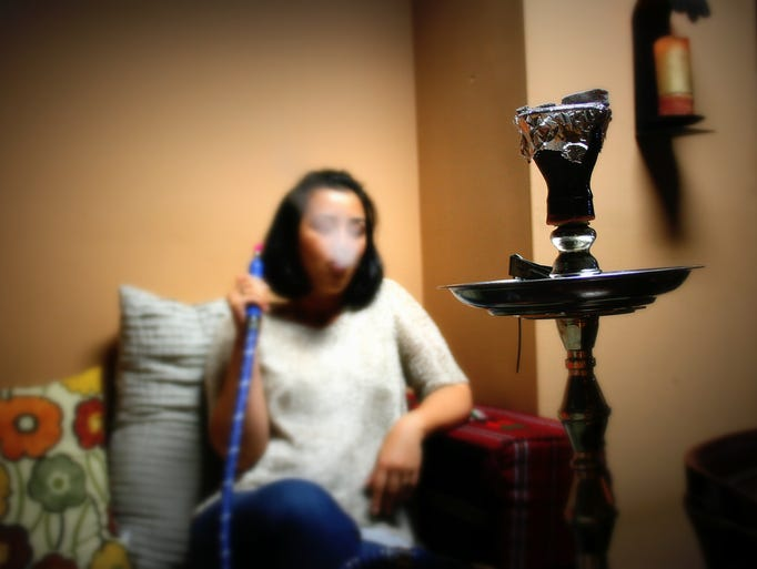 A hookah lounger-goer exhales a gust of the smoke from