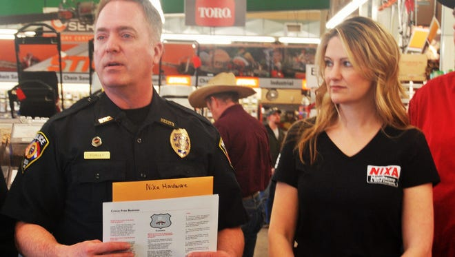 Officer Brent Forgey presents a certificate and window decal to Christi Fairchild, of Nixa Hardware, for the company's completion of the Crime-Free Business Program.