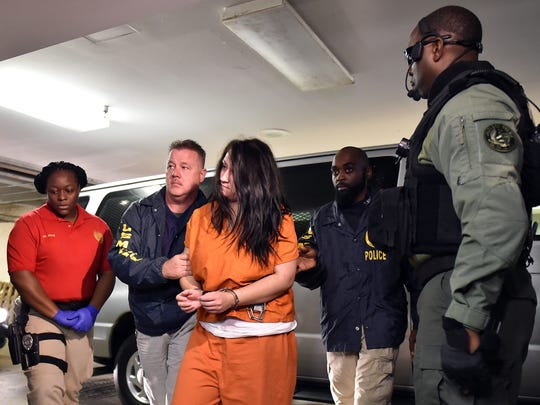 Jamison Townsend is escorted by U.S. marshals into Jackson Police Department. Townsend and her accomplice, Joshua Garcia, are charged with three counts of capital murder each for the deaths of three men at Bill's Pawn Jewelry Coin/Stamp Exchange in December.