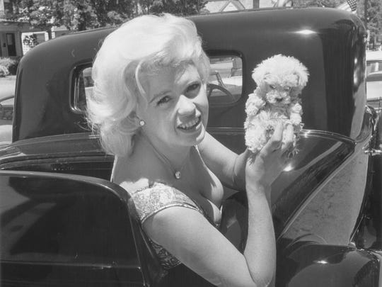 Jayne Mansfield holds her pet poodle aloft during the Indianapolis 500 Festival parade in 1961.       Photo by Indianapolis Star photographer William A. Oates