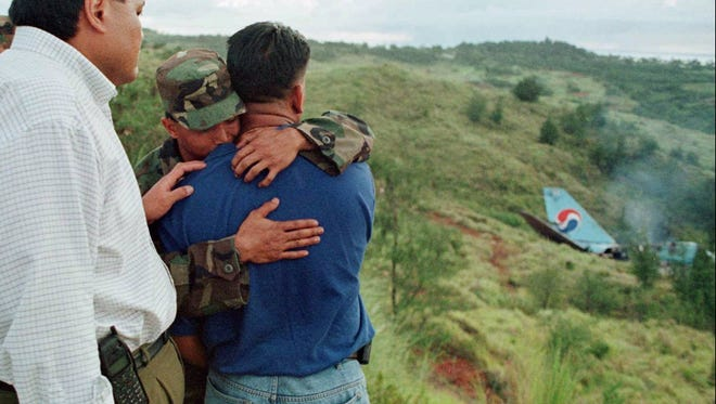 An unidentified man is consoled by a U.S. Marine looks at the tail section of Korean Air jumbo jet which crashed early Wednesday, Aug. 6 1997. The ill-fated flight 801 with 254 passengers and crew on board slammed into a shallow hillside outside Agana, Guam, while approaching to land at Won Pot International airport.