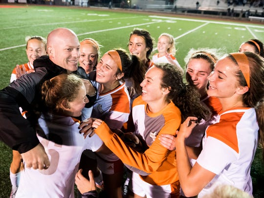 Central York players mob head coach Eric Webb after the Panthers defeated Northeastern 1-0 to win their third YAIAA title in four years on Thursday, Oct. 19, 2017.