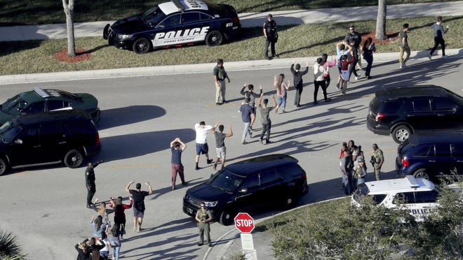 In this Feb. 14, 2018 file photo, students hold their hands in the air as they are evacuated by police from Marjory Stoneman Douglas High School in Parkland, Fla., after a shooter opened fire on the campus. The police response to the Florida high school massacre was delayed because school officials rewound a school surveillance video, making officers think the gunman was still in the building, the South Florida Sun-Sentinel reports.