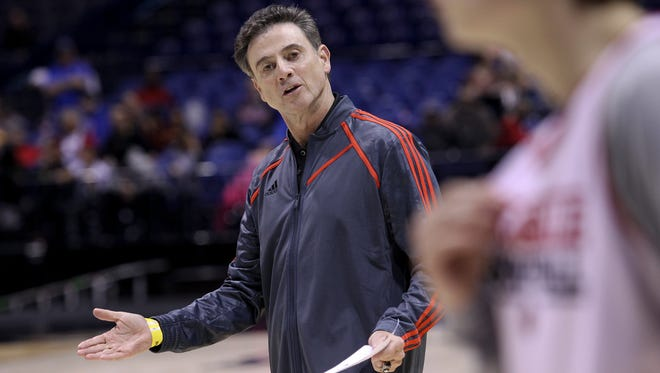 U of L head coach Rick Pitino instructs his players as they practice ahead of their Sweet 16 match up with Kentucky at the Lucas Oil Stadium in Indianapolis. Mar. 27, 2014