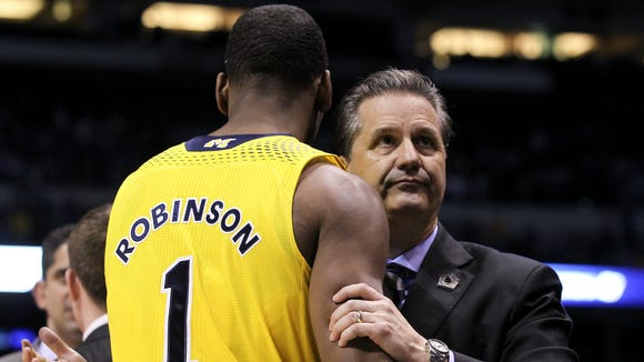 UK head coach John Calipari, right, hugged Michigan's Glenn Robinson III,  after they defeated them during the Elite 8 game at the Lucas Oil Stadium in Indianapolis. Mar. 30, 2014