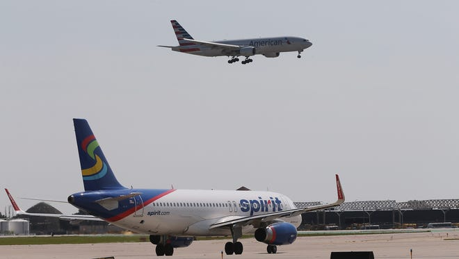 An American Airlines jet prepares to land as a Spirit Airlines jet taxis at O'Hare International Airport on September 19, 2014 in Chicago, Illinois.