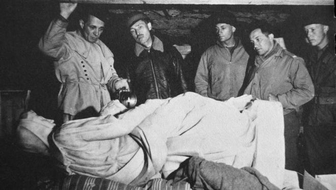 Dansville's William Kelly stands at far right inside a salt mine in Austria looking at Michangelo's Madonna and Child sculpture in 1945. At left are some of the now famous Monuments Men. The small corps of mostly middle-aged men and a few women interrupted careers as historians, architects, museum curators and professors to protect and recover priceless works of art.