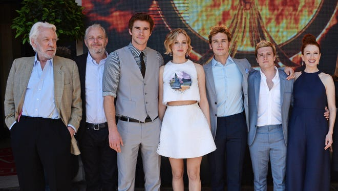"""""""The Hunger Games"""" crew come to Cannes. From (L to R) Donald Sutherland, director Francis Lawrence, Liam Hemsworth, Jennifer Lawrence, Sam Claflin, Josh Hutcherson and Julianne Moore appear at  """"The Hunger Games: Mockingjay Part 1"""" photocall at the Majestic Barriere on May 17, 2014 in Cannes, France."""