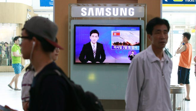 A TV news program reports on missiles launched by North Korea at Seoul Railway Station in Seoul on July 13, 2014.