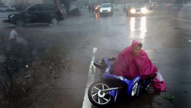 High winds from Typhoon Rammasun in south China's Hainan province take down a motorbike rider on July 18, 2014.