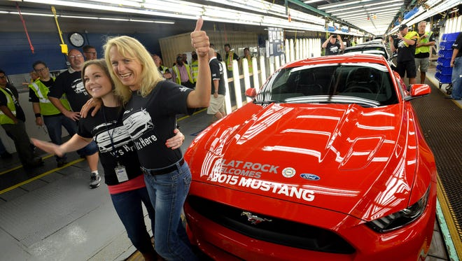 Sarah Johnson and Mary Bourke, workers at Ford's Flat Rock plant in Michigan, as the first redesigned 2015 Ford Mustang rolls off the line on Wednesday.