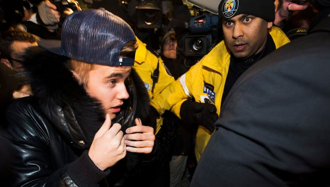 Canadian musician Justin Bieber is swarmed by media and police officers as he turns himself in to city police for an expected assault charge, in Toronto, on Jan. 29, 2014.