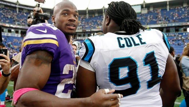Minnesota Vikings running back Adrian Peterson (left) meets with Carolina Panthers defensive tackle Colin Cole (91) after Sunday's game.
