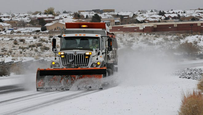 A Department of Transportation plow and sanding truck heads up Paseo del Norte in Albuquerque, N.M., on Nov. 24.