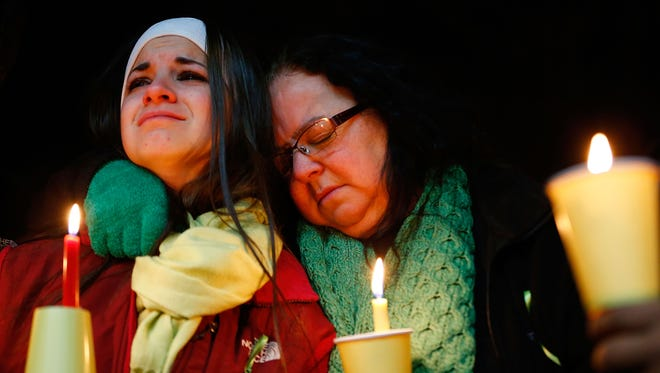 Donna Soto (R), mother of Victoria Soto, the first-grade teacher at Sandy Hook Elementary School who was shot and killed while protecting her students, hugs her daughter Karly while mourning their loss at a candlelight vigil in honor of Victoria.