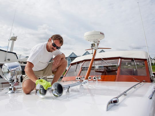 Mike Krug, of Florida, polishes the horn on a 1955 Chris Craft Conqueror during the Blue Water Classic and Antique Boat Show Saturday at the River Street Marina in Port Huron.