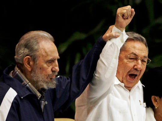 FILE - In this April 19, 2011 file photo, Fidel Castro, left, raises his brother's hand, Cuba's President Raul Castro, center, as they sing the anthem of international socialism during the 6th Communist Party Congress in Havana, Cuba. Cuban President Raul Castro has announced the death of his brother Fidel Castro at age 90 on Cuban state media on Friday, Nov. 25, 2016. (AP Photo/Javier Galeano, File)