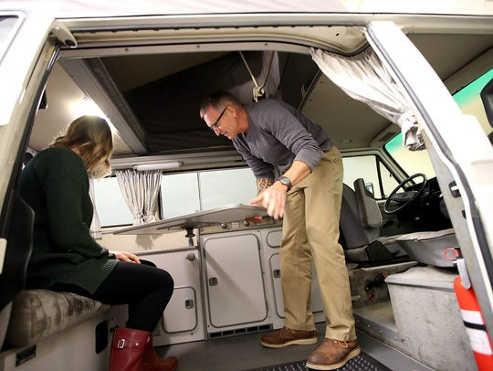 "PacWesty's Greg Dronkert swivels the dining table into position as he and Nora Phillips give a tour of the amenities in the Volkswagen Westfalia camper van named ""Burt"" on Bainbridge Island."