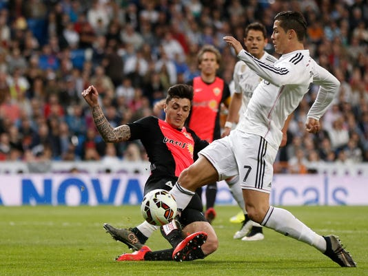 Real Madrid's Cristiano Ronaldo duels for the ball with Joaquin Navarro Jimenez, from Spain, left, during a Spanish La Liga soccer match between Real Madrid and Almeria at the Santiago Bernabeu stadium in Madrid, Spain, Wednesday, April 29, 2015. (AP Photo/Daniel Ochoa de Olza)