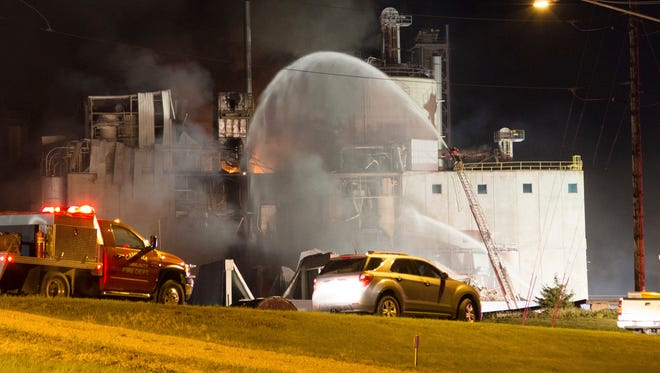 This Thursday, June 1, 2017, photo provided by Jeff Lange shows firefighters at the scene following an explosion and fire at the Didion Milling plant in Cambria, Wis. Recovery crews searched a mountain of debris on Thursday following a fatal explosion late Wednesday at the corn mill plant, which injured about a dozen people and leveled parts of the sprawling facility in southern Wisconsin, authorities said.