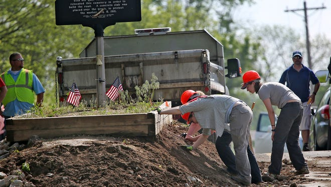 UIndy graduate students gently sift through dirt at the grave site of Nancy Kerlin Barnett, as workers move to temporarily move her remains from the middle of E. 400 S. near Amity, Wednesday, May 11, 2016.  Johnson County highway crews closed County Road 400 South near Amity while a UIndy archaeologist digs up the resting place of Barnett, who lies in the middle of two lanes of country road. Barnett, a farmer's wife, died in 1831. Her last request was to be buried on this site, which was then a grassy hill near Sugar Creek. The area soon became a cemetery. Years passed and the county decided to move the cemetery to make way for a road. As crews removed the other graves, Barnett's grandson armed himself and stood vigil until the crews decided to just build the road on either side. It's been that way ever since, until now. Archaeologist Chris Schmidt and his students will move BarnettÕs remains temporarily and do some tests on the remains. Later this month, crews will rebuild and lower the burial mound, widen the road and build a new protective barrier for the 185 year old grave. When thatÕs done, Barnett will be returned to her resting place. The site has been the victim of not frequent, but regular traffic accidents over the years. The goal is to make the grave safer for drivers and BarnettÕs memory.