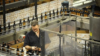 Inspector Chris Cooper checks out the label placement on Blackstone bottles as they move along the assembly line in Blackstone's bottling facility in 2015.