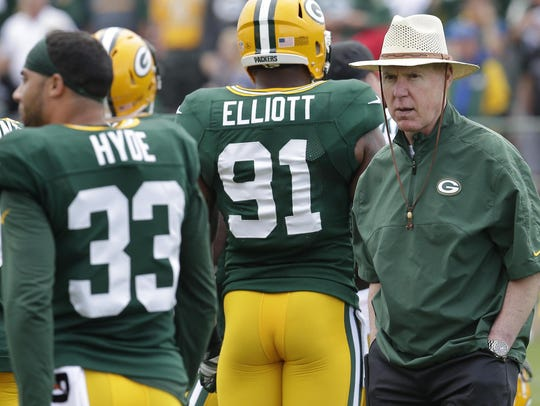 Packers general manager Ted Thompson, right, watches