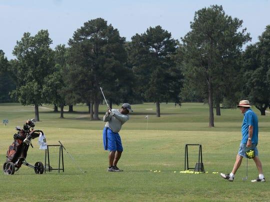Dan Maloney watches as Melvin Singleton drives a ball