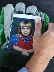 Dave Triola held a photo of a 7-year-old Emily Ernspiker