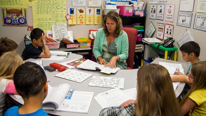 Interventionist Amy Martin works with students in a tier 3 third-grade class at Sunset Hills Elementary School on Thursday, March 20, 2014 in Surprise, Arizona.