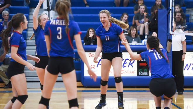 Parker players celebrate after winning a set during their high school volleyball match on Thursday, Oct. 12, 2017 at Parker High School.
