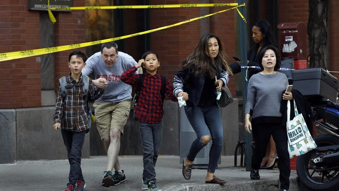 Parents pick up their children from Public School 89, close to where a gunman emerged from a crashed Home Depot rental truck after plowing down bike riders on Tuesday, Oct. 31, 2017. The New York Police Department reported one man was in custody after initial reports of gunfire set off a mad scramble in the downtown area. (Carolyn Cole/Los Angeles Times/TNS)
